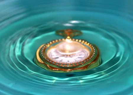 water and vintage golden watch Standard-Bild