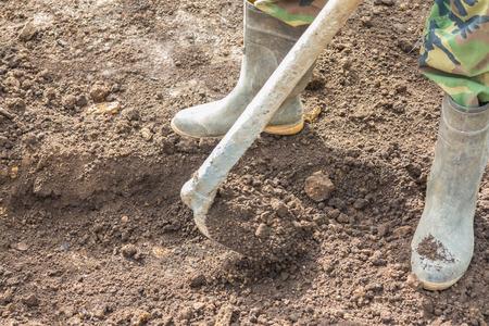 dig: Worker using hoe dig the soil.
