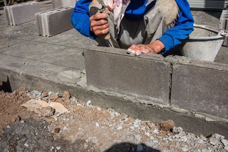 layers levels: Worker installing  brick for construction site.