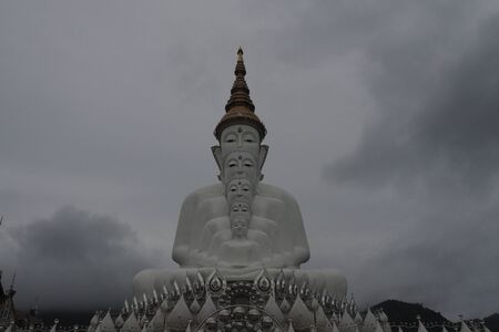 white Buddha statue with clouds.