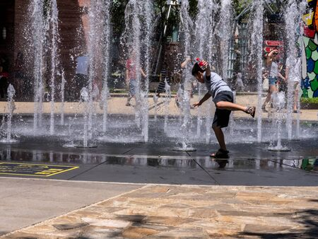 Children playing with water in park fountain