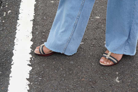 woman's foot stands behind a white line on the road.