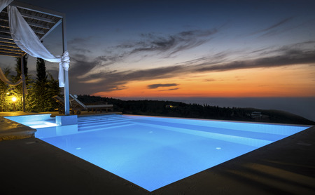 Luxurious Infinity Pool overlooking the Greek coast during Sunset, Lefkada, Greece. Stock Photo