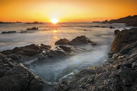 Romantic sunset over rocky coast and soft silky water, Sardinia, Italy. Standard-Bild