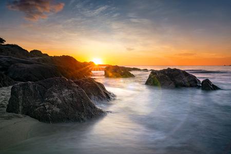 Romantic sunset over sandy beach and soft silky water, Sardinia, Italy.