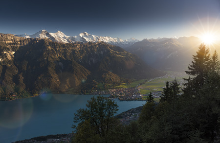 Idyllic view over Interlaken, Lake Brienz and the Swiss Alps during sunset, featuring famous Eiger, Moench & Jungfrau, Bernese Oberland, Switzerland.
