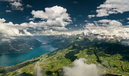 Aerial shot of Bernese Alps, lush valley and Lake Thun, Berner Oberland, Switzerland. Standard-Bild - 122333522