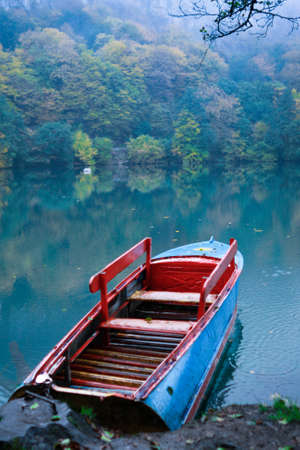 Boat on wood lake in the autumn Stock Photo