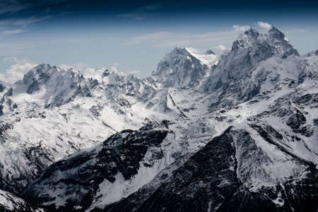 Severe mountains are covered by snow under dramatic sky