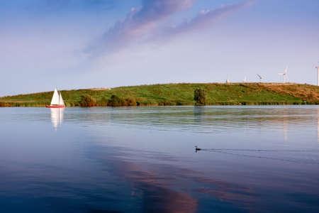 Sailing against wind turbines a quiet evening Stock Photo