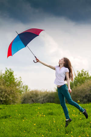 Girl with colored umbrella jumping in a green meadow photo