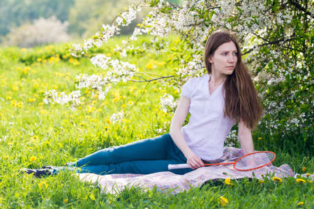 Beautiful young women sitting under blossom tree with badminton racket in her hand Stock Photo