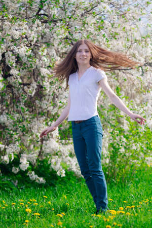 young girl turning head and smiling with blossom tree behind Stock Photo