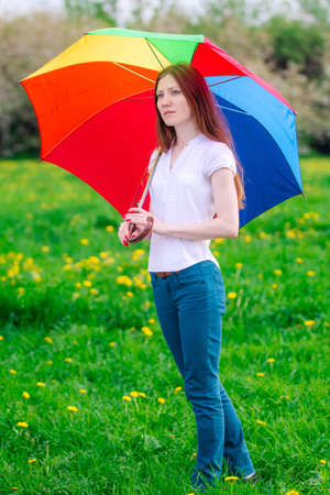 Girl with colored umbrella in a green meadow