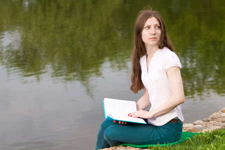 beautiful girl reading book on the bank
