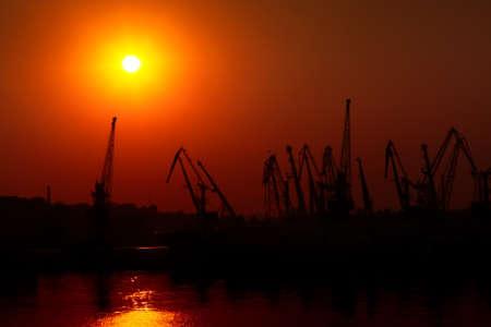 Hoisting crane silhouettes on sunset