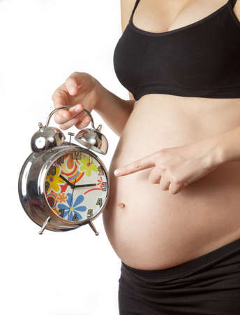 Pregnant woman belly pointing at alarm clock photo