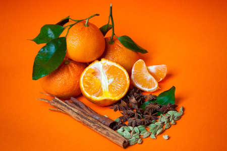 Mandarins with cinnamon, star anise and cardamom orange background
