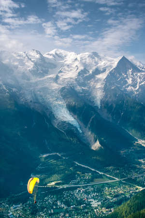 paraglide: Yellow paraglide over Alps green valley