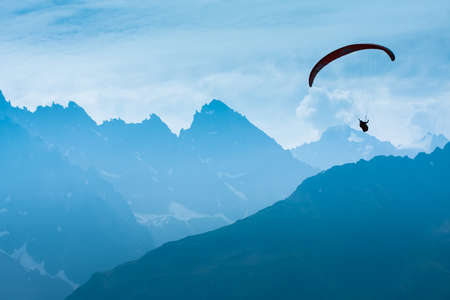 Paraglide shadow figure over Alps peaks