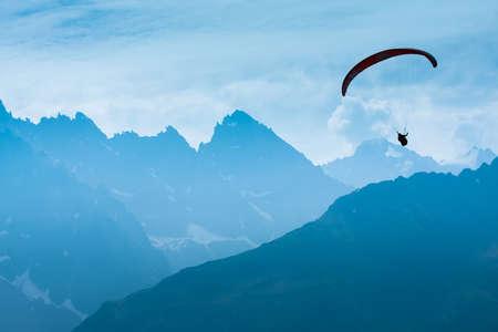 parapente: Parapente sombra figura sobre picos Alpes Foto de archivo