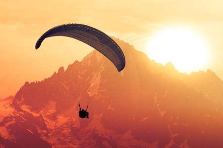 アルプスのピーク上のセピアのパラグライダーで飛ぶシルエット