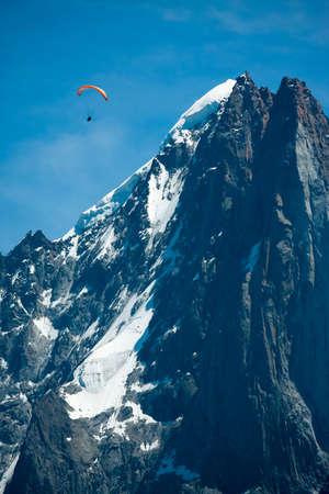 Red paraglide over Alps peaks