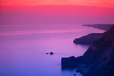 Purple and pink sunset over ocean shore and mountains