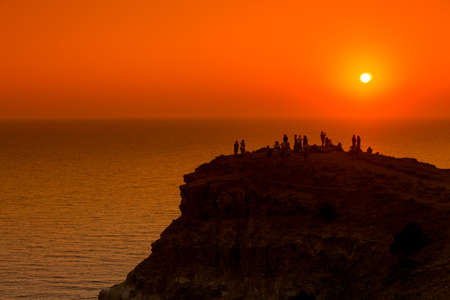 People silhouettes on the sunset on the cliff over the sea Stock Photo