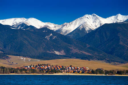 Lake and village at Tatras mountains and white peaks above