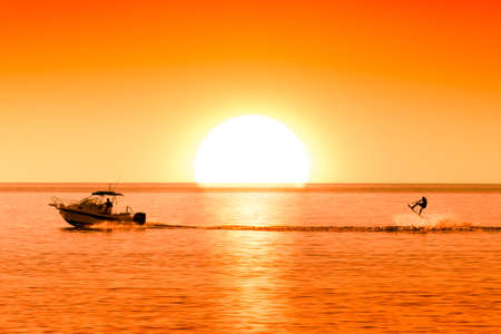 silhouette of motor boat and wakeboarder at sunset performing crazy trick Stock Photo