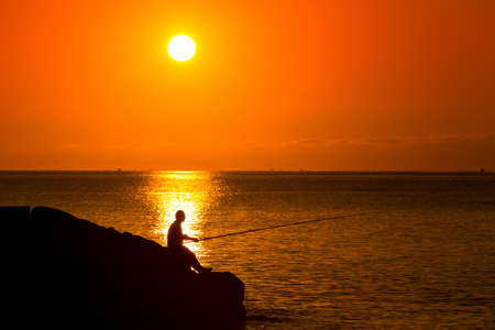 silhouette of fisherman fishing on the sunset Stock Photo