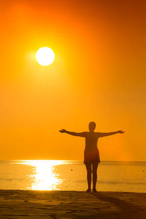 silhouette of woman practicing yoga with raised arms on the sunset Stock Photo