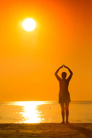 chi kung: silhouette of woman practicing yoga with raised arms on the sunset Stock Photo