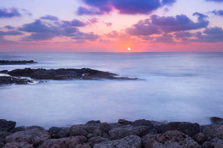 Purple and pink sunset over ocean rocky shore