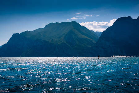Windsurfers and mountains at Garda lake, Italy Stock Photo