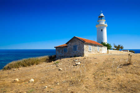 old white lighthouse on the rocky sand hill