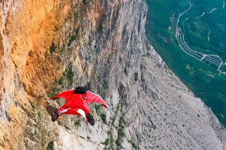 cliff jumping: Wingsuit B.A.S.E. jumper jumps off a cliff in Italy Stock Photo