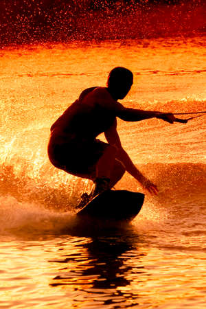 wakeboarding: Sepia wakeboarder silhouette at lake waves performing crazy trick Stock Photo