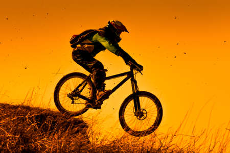 Downhill mountainbike rit bij zonsondergang Stockfoto