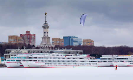 Winter snowkiting at Moscow North River Port and ships behind kiteboarder Stock Photo