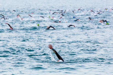 Triathletes swim on start of the Ironman triathlon competition at Calella beach