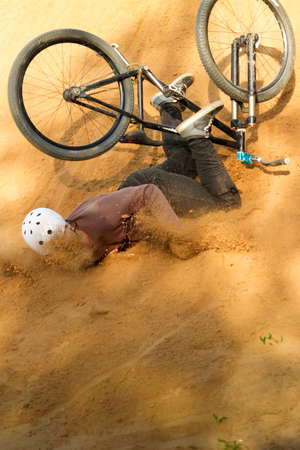 bmx bike: biker is falling from his mountain bike to the sand at the contest