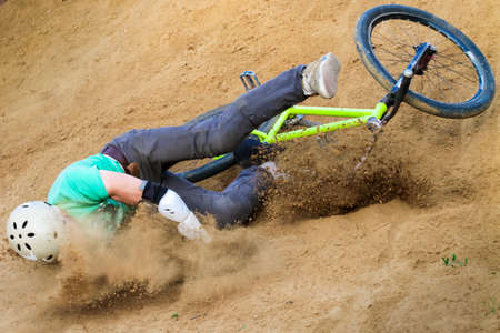 crash helmet: biker is falling from his mountain bike to the sand at the contest