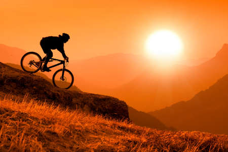 recreational vehicle: silhouette of downhill mountain bike rider at orange sunset