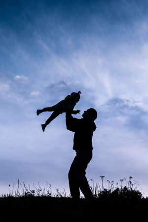 silhouette of father with baby flying over his head