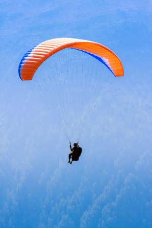 Red paraglide in blue sky over Alps peaks