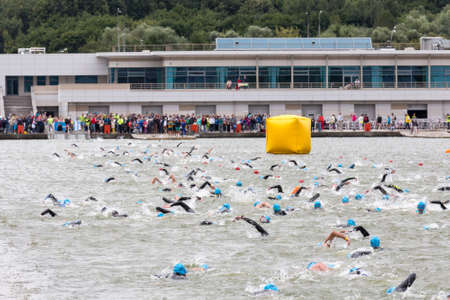 Triathletes swim on start of the triathlon competition in Moscow River and viewers behind the scene