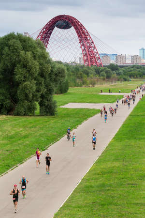 Triathletes run during triathlon competition in Moscow with cable-stayed red Jivopisny Bridge behind, Moscow, Russia