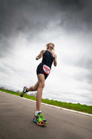 Woman triathlete runs during triathlon competition, bottom view, Moscow, Russia